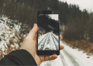 Man making a photo of a forest road in winter